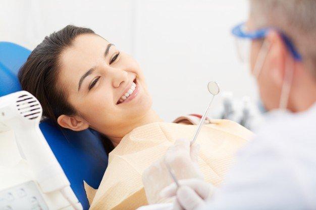 Mulher nova que recebe check-up odontológico Foto gratuita